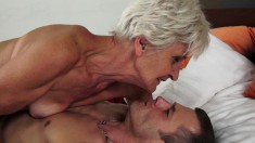 Naughty granny surrenders her pussy to a horny young stud on the bed