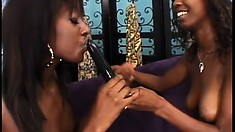 Chocolate lezzo reaches a loud orgasm while standing bent over the back of the couch