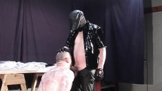 Sadistic master wraps up his slave in cellophane as he makes him suck