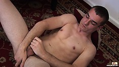 He lays back on the floor rubbing his cock and fingering his ass